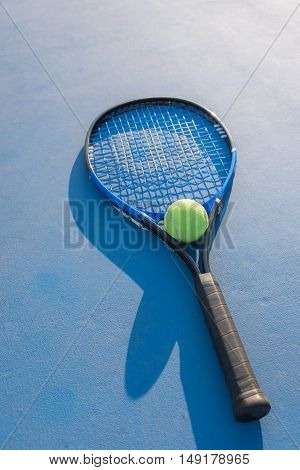 Tennis Ball and Racket on tennis court.