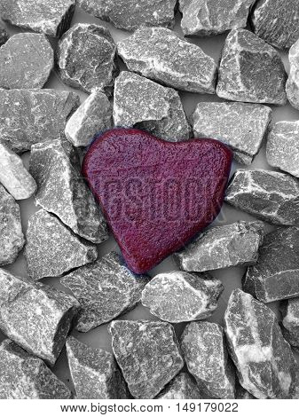 Red heart made of stone between grey stones