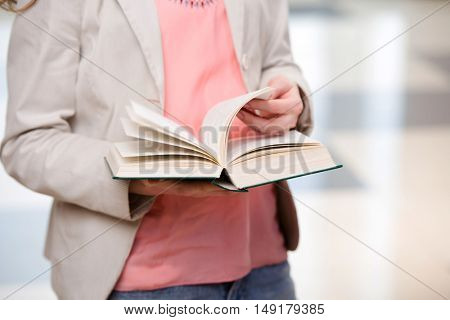 Young student reading book in preparation for exams