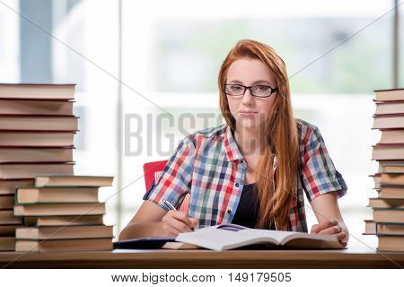 Student with stacks of books preparing for exams