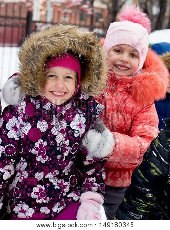 closeup portrait of Happy laughing children in winter clothes outside playing in the snow drifts in the winter - Russia, Moscow - February 25, 2016