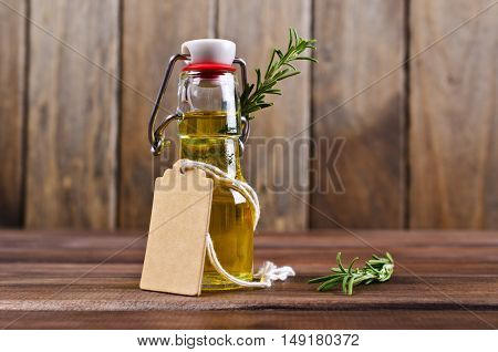 Oil with dry leaves of rosemary on the wooden background. Selective focus.