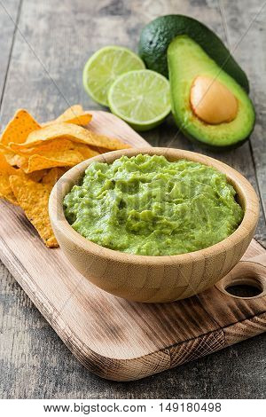 Nachos, guacamole and ingredients on wooden table