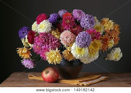 Autumn bouquet of asters and chrysanthemums on a dark background. Still life with flowers and Apple.