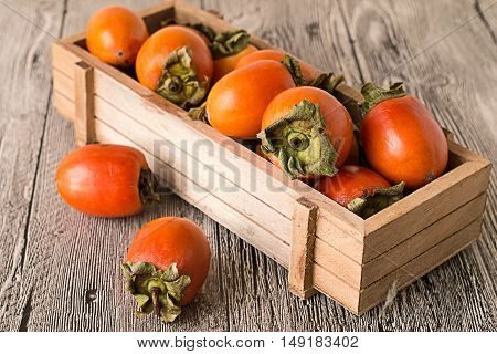 Juicy ripe persimmon in a wooden box on a gray wooden background.