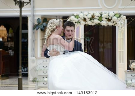 Wedding Couple In The Restaurant Is Dancing. Beautiful Model Girl In White Dress. Handsome Man In Su