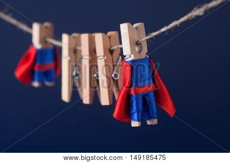 Super team concept photo with clothespin superheroes in blue suit and red cape. Big small powerful heroes. Dark background. soft focus. macro view