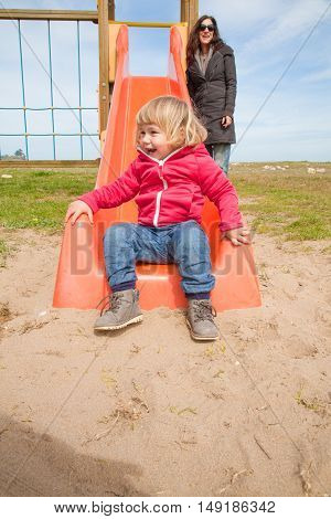 two years old blonde happy baby sitting down of orange plastic slide in outdoor playground laughing next to mother