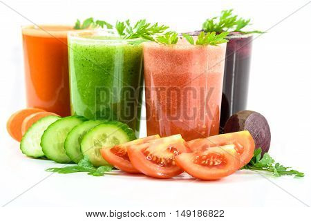 Four vegetable juices in glasses with parsley and vegetables isolated on a white background