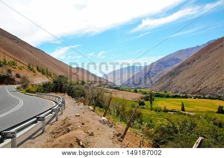 Long shot of the Elqui Valley with a street to the left and a blue sky with some white clouds in Chile, South America