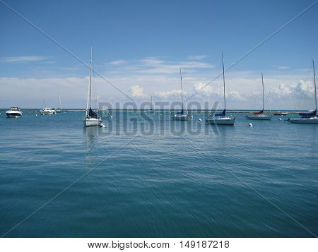 Small tourist boats at luxury yacht club marina water front during sunny summer day with blue clear sky and sea background. Recreation, relax, travel, sailing, yachting, regata concept with empty copyspace