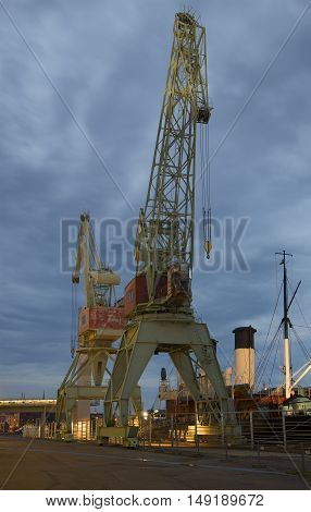 KOTKA, FINLAND - AUGUST 09, 2015: Two old harbour crane on the pier of Maritime centre of Velamo, summer night. Tourist landmark of the city Kotka, Finland