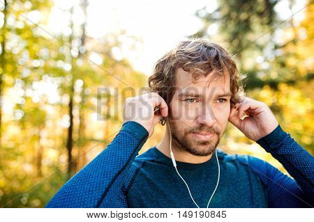 Young handsome runner putting earphones in his ears, listening music, outside in sunny autumn nature