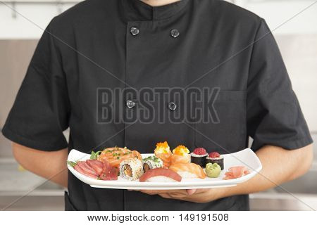 Male chef holding a plate full of sushi at the kitchen