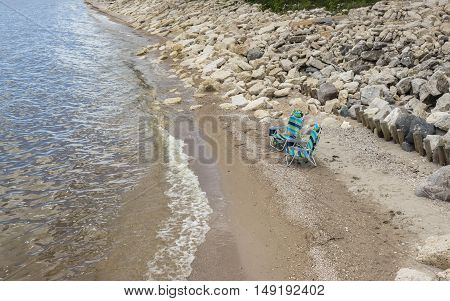 horizontal image of two empty striped lawn chairs sitting on the beach along the shoreline with waves lapping up on the sandy beach with large stones and rocks on the embankment in the background