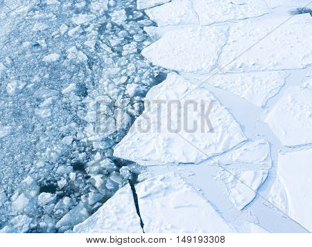 Beautiful ice on the river and a lot of cracks and visible blue clear water