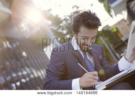 Signing business documents while sitting outdoors