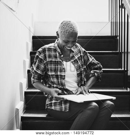 African Woman Laptop Gadget Sitting Stairway Concept