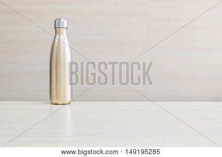 Closeup gold color of aluminium flask for keep hot water on blurred wooden desk and wall textured background under window light