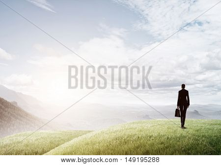 Elegant businesswoman standing on green hill and looking ahead