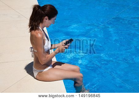 Side Woman Sitting On Edge Of Pool Using Mobile Phone