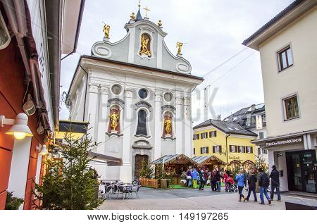 Brunico Italy 14 December 2014: christmas markets in the central square of San Candido with the main church's facade on background