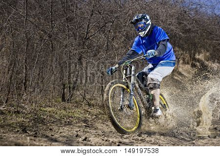 Extreme mountainbiker rides on path in mud