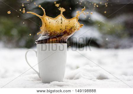 Freeze splashing coffee cup on the snow