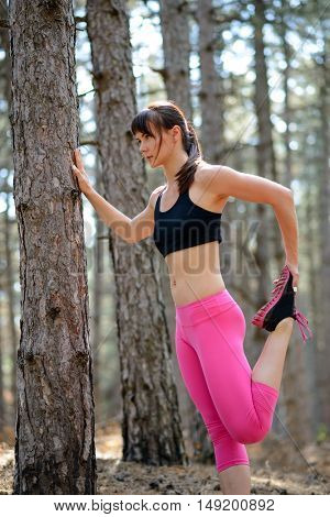 Young Fitness Woman Stretching her Legs in the Pine Forest. Female Runner Doing Stretches Outdoor