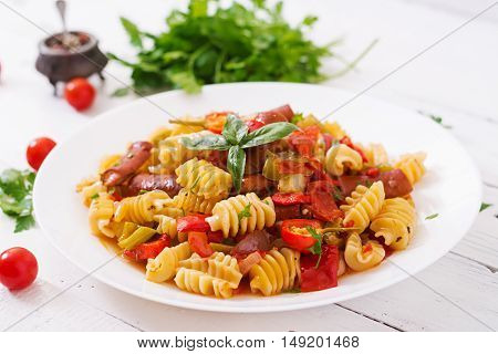 Pasta With Tomato Sauce With Sausage, Tomatoes, Green Basil Decorated In White Plate On A Wooden Bac