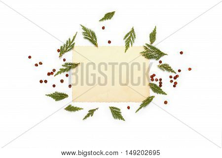 Green plants of juniper evergreen and red berries arranged around vintage card on white background. Flat lay top view. Christmas concept.