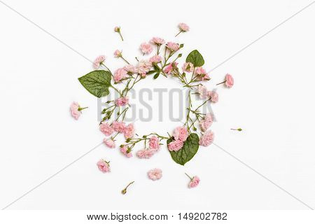 Floral round frame on white background. Flat lay top view. Ornament with rose flowers and green brunnera leaves with space for text.