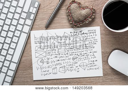 Keyboard, notepad and coffee cup on wooden desk