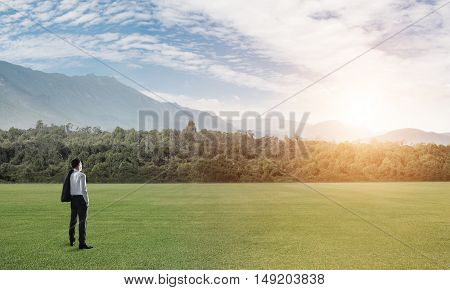 Elegant businessman standing on green field and looking ahead