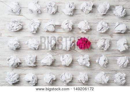 Set of crumpled white paper balls with one colorful ball.