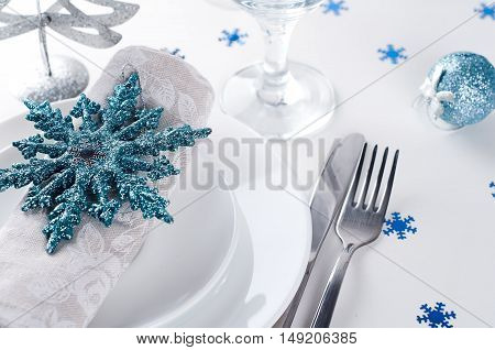 Christmas table setting in blue and silver colors with decorations.