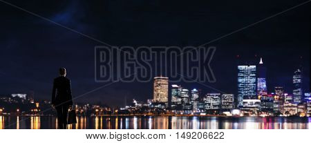 Businesswoman standing with back against night city panoramic view.