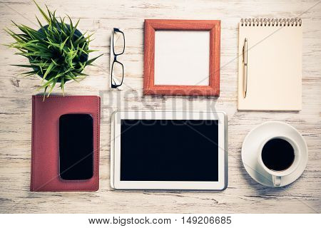 Still life photo of tablet, notepad, coffee, glasses on wooden table.