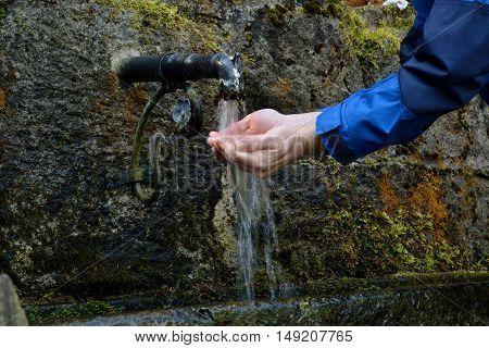 Person refreshed at a drinking water source - close-up