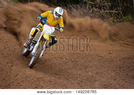 Rider driving in the motocross race on sand road