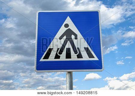 Traffic sign pedestrian crossing under cloudy blue sky