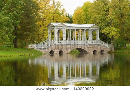 Marble bridge is reflected on the surface of the lake.