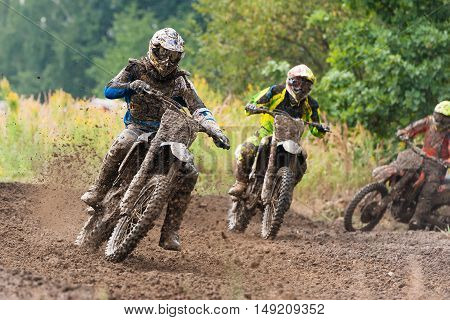 Motocross riders in the race on mud road