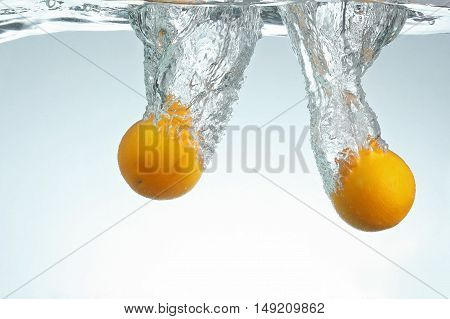 Two Oranges drop in water with splash