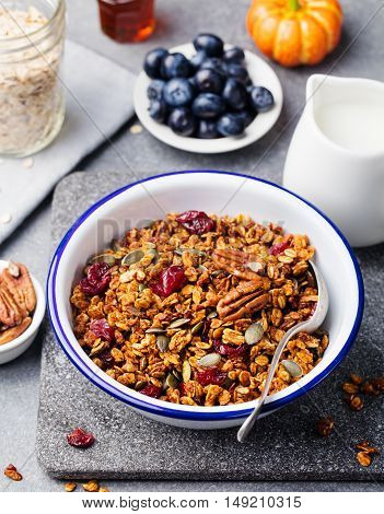 Healthy breakfast. Fresh pumpkin granola, muesli with seeds, pecan nuts, cranberries and maple syrup in white bowl