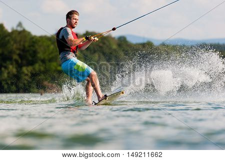 Wakeboarder surfing across a lake on summer day