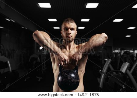 Fitness man doing a weight training by lifting heavy kettlebell. Yong athlete doing kettlebell swings. Bodybuilder lifting kettlebell