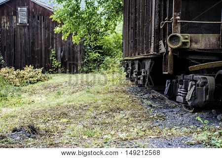 abandon railroad car and wood building in rural setting