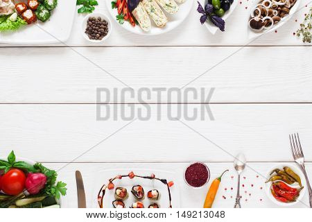 White wooden table with traditional food frame, flat lay. Top view on table with different tasty snacks, free space for advertisement or text