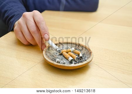 Female hand with cigarette rest on the ashtray